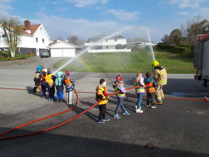 Barn spyler med brannslange